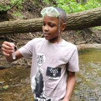 Student stands in stream and looks at sample of water